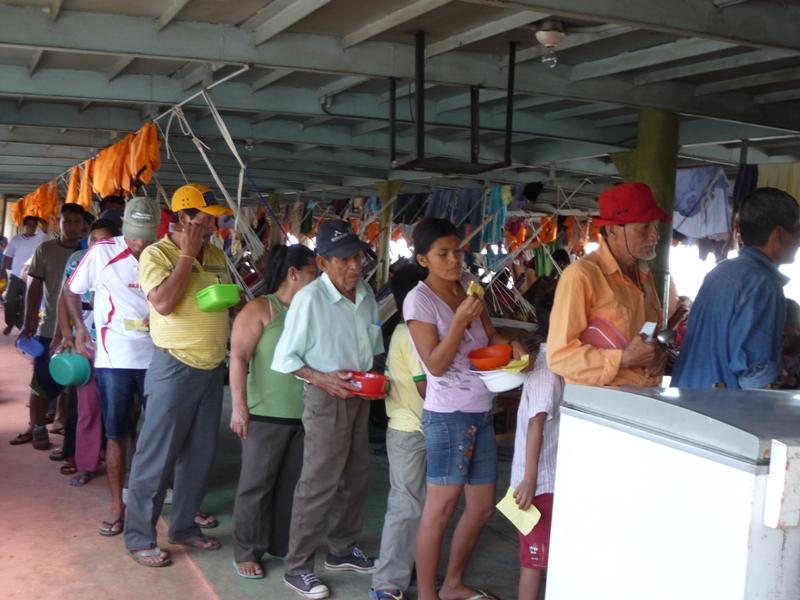 En file indienne,boite en plastique à la main, tous les passager vont chercher le repas